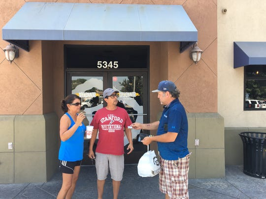 J.J. Macrae hands out a Mr. Takeout business card to potential customers in Visalia.