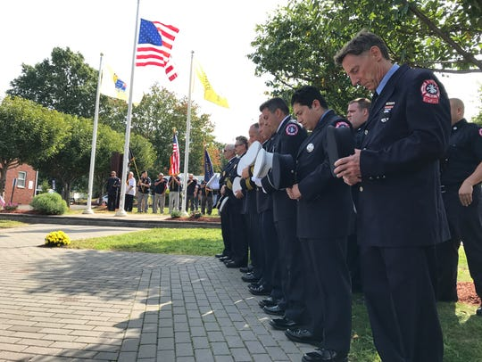 Belleville firefighters bow their heads during a prayer
