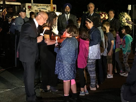 Mayor Mike Ghassali helps a child light a candle at the borough's 9/11 ceremony on Monday, Sept 11, 2017.