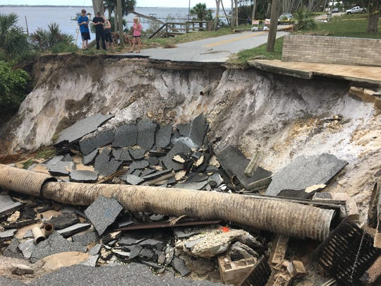 Water gushed from a pipe in a collapsed section of Indian River Drive and Sunset Terrace in Cocoa Monday, where police monitored a cordoned-off the area.