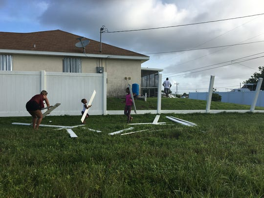 The Forbes Family cleans up their damaged fence after Hurricane Irma whipped their Cape Coral home Sunday night.