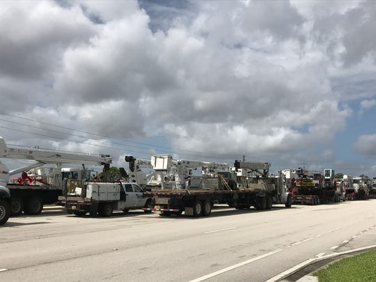 A line of utility trucks from Texas wait to learn where they will be deployed to help restore county.