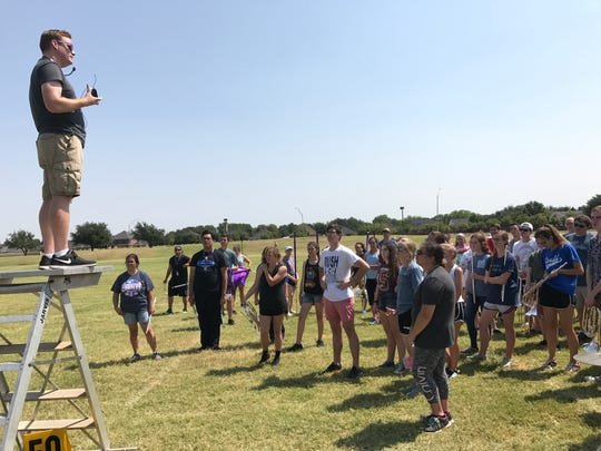 Brandon Houghtalen, associate director of bands, talks to Big Purple Marching Band members after practice Monday at Abilene Christian University. The band is preparing for the first home game in Wildcat Stadium.