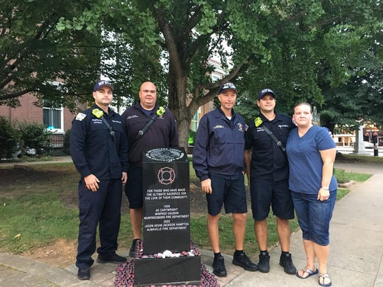 Murfreesboro Fire Rescue Department firefighters pose with local resident Tavia Bloom after placing rocks on the firefighter memorial in Murfreesboro's public square early Monday morning. Bloom painted 343 rocks, one for each firefighter who died in the terror attacks on Sept. 11, 2001.