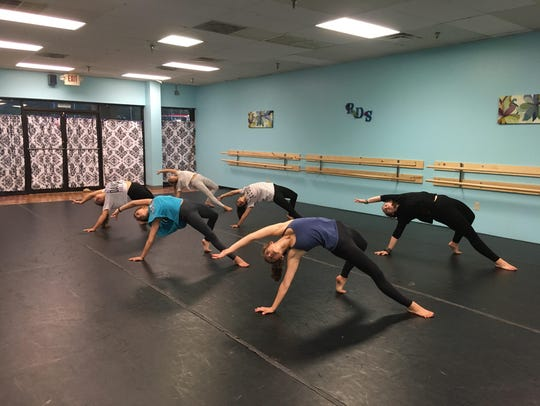 Dancers practice choreography that includes arching