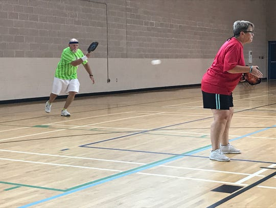 Mike Hogg, left, returns a pickleball shot as his wife and playing partner Sue Hogg watches the net on Friday, Sept. 15, 2017, at the Vickrey Resource Center in Pensacola. The couple participated in pickleball, one of 21 events at the Pensacola Senior Games.