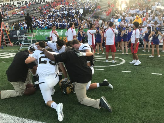 Abilene High defensive players and coaches kneel in prayers before Friday night's game against crosstown rival Cooper High.