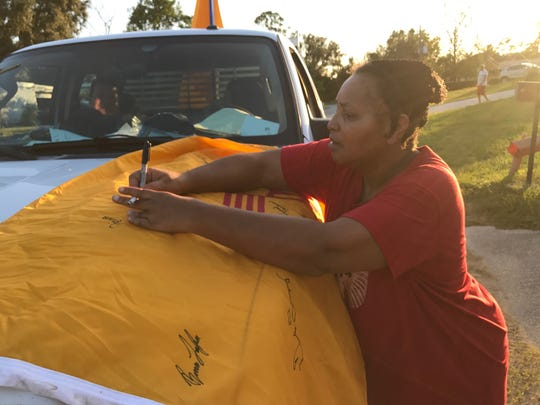 A Florida resident signs the New Mexico flag that Joseph Bizzell flew during the Hurricane Irma storm.