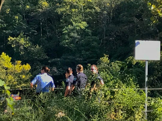 "Knoxville Police Officers and an Emergency Medical Technician talk  on a cliff-side overlooking Fort Dickerson Quarry. A rescue boat was searching the water below after a report of a possible drowning. Police officers barred the public from the overlook, citing an active ""crime scene."""
