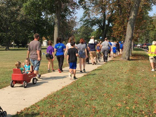 Walkers head to Birchwood Mall from Lakeside Park for the 23rd Walk for Kids' Sake and Community Roof-Sit. Blue is the color that symbolizes child abuse prevention.