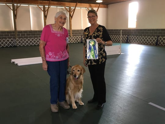 Cherie Berger, left, accepts an obedience award with