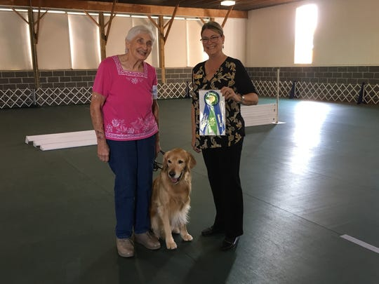 Cherie Berger, left, accepts an obedience award with her dog, Spruce, at a dog show organized by the St. Clair County Kennel Club. Berger has been  participating in dog shows since 1952.