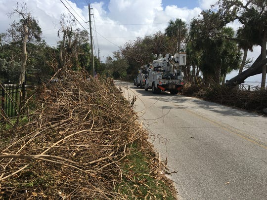 Yard debris and Florida Power and Light contractors line South Tropical Trail in Merritt Island.