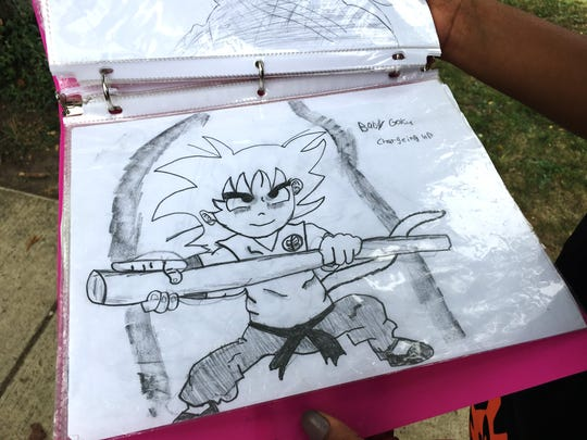 A family member holds a drawing by Jaylen Brock, 14, who loved making art.