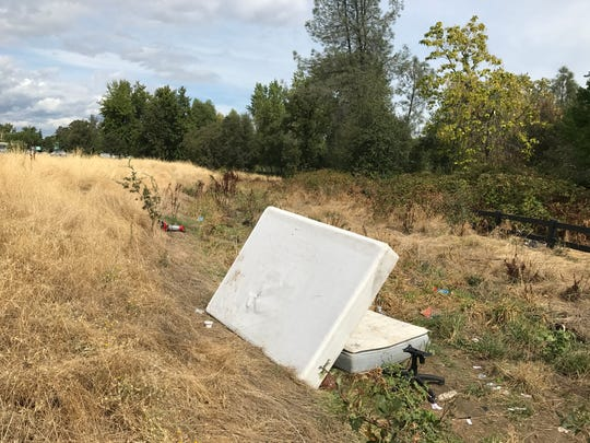 A spring box partially covers a mattress and office chair at a homeless camp on an empty lot where Hill Country proposes to build a medical facility and transitional housing for homeless youths.