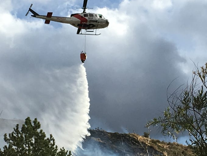 A helicopter drops water on the Woodchuck Fire west