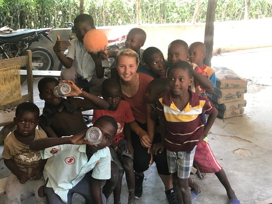 Katrina Pokorny poses with children in Haiti while