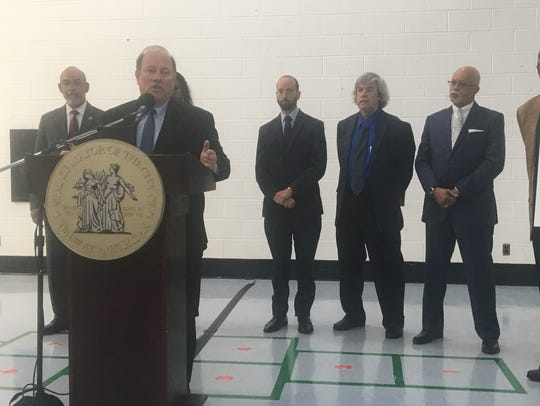Detroit Mayor Mike Duggan stands with other community