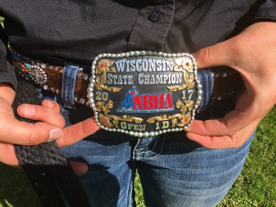 Olivia Helminiak shows off the belt buckle she earned for winning the open division at the National Barrel Horse Association's state finals in Elkhorn.