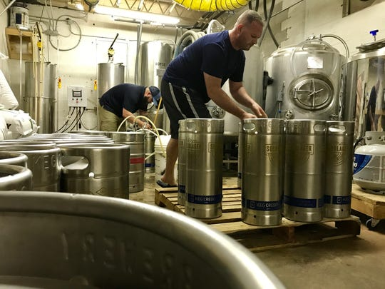 Alex Nicolato, right, and James Bridwell fill kegs at their brewery, Sockdolager Brewing Co., on Sept. 13, 2017.