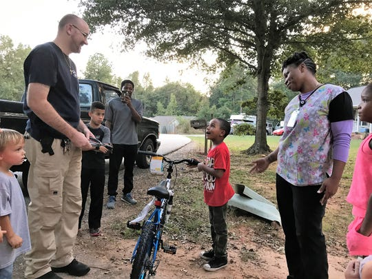 Walter Lanier, president of Homeland Park Community Watch, gives Cayden Dennis a new bike to replace his stolen one.