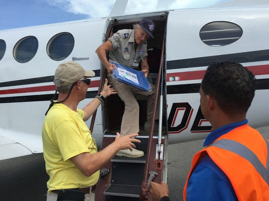RAM Founder Stan Brock takes a tarp from RAM Medical Director Dr. Chris Sawyer while boarding a plane in Puerto Rico.
