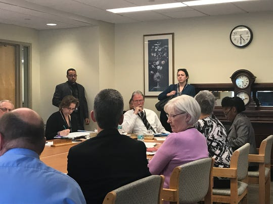 CEO Teresa McQuaid third from left in foreground), interim CEO of Greystone Park Psychiatric Hospital, fields questions from the state-run hospital's Board of Trustees chairman Eric Marcy (center, in background) during a trustees meeting on Sept. 21, 2017.