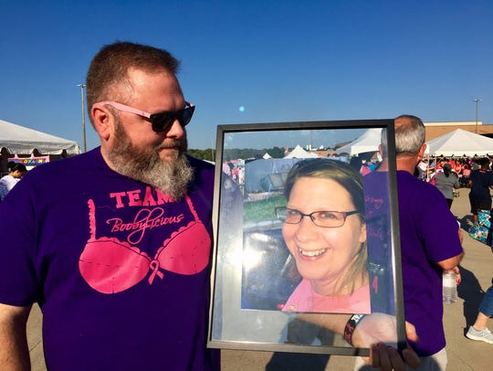 Rob Rowland holds a picture of his wife, Michelle,