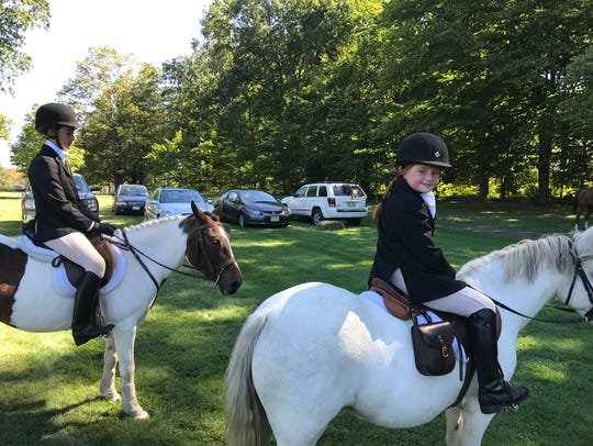 Adult and child equestrians rode on the grounds of