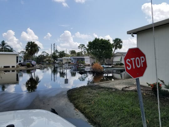 The Imperial River spills its banks into the streets of Imperial Bonita Estates on Monday