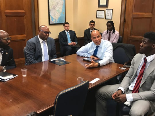 Sen. Cory Booker speaks to Detroit Lions cornerback Johnson Bademosi during a discussion about criminal justice reform also attended by Philadelphia Eagles safety Malcolm Jenkins, far left.