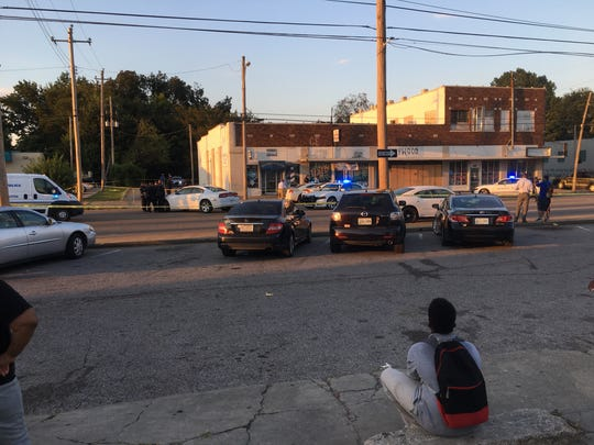 "Marquaveon Crews, 12, watches Memphis police officers investigate a shooting that took place on Chelsea Avenue in North Memphis. Four people were shot. The boy's mother, Marquita Lockett, said she's concerned. ""They need to change. They need to do something for the kids out here. They're dying. Our kids dying."""