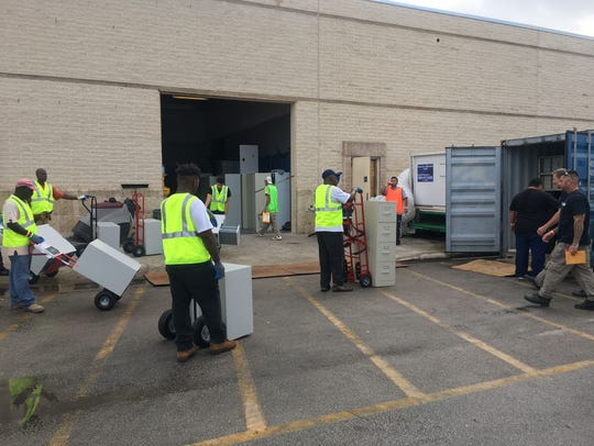 Clean office furniture is loaded in cargo containers