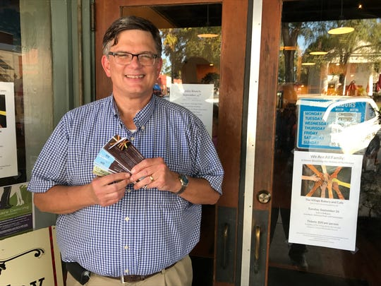 The Rev. Keith Ray, pastor of Clemson United Methodist church, sells tickets to a fundraiser for hurricane relief at the Village Bakery and Cafe in Pendleton