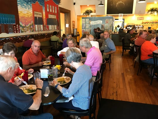 Donors, who paid $20 per person, enjoy a meal of Syrian chicken, rice and green beans at a hurricane fundraiser at the Village Bakery and Cafe in Pendleton