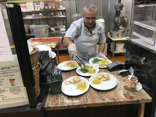 Abdul Karkour prepares plates to be served at a fundraiser