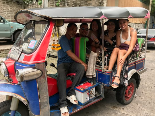 Take a ride in a tuk tuk through the streets of Bangkok.