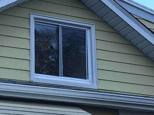 Holes can be seen in several windows of a Marion Avenue