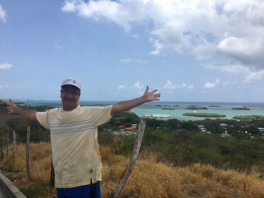 Dr. Ivan Figueroa spreads his arms in La Parguera, Puerto Rico in August, just weeks before Hurricane Maria devastated the island.