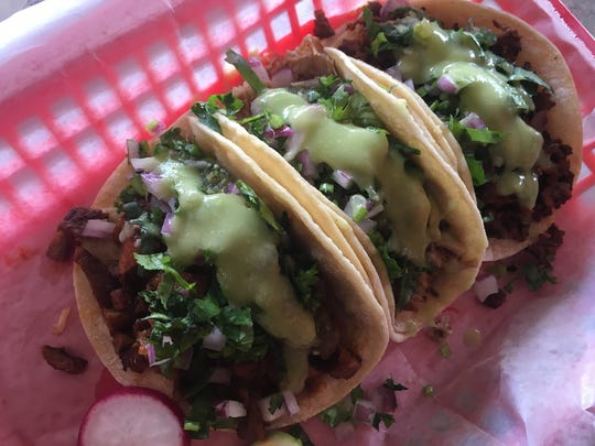 Tacos from La Fogatita Mexican Grill come with a green salsa, red onion and cilantro, as well as lime wedges and radishes.