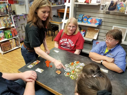 Anne-Marie De Witt, right, shows gamers how to play a new game designed by her husband, Hotshots, at The GameBoard in Sheboygan on Sept. 19.