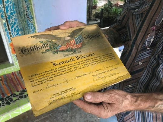 George Wilcoxen holds one of his most prized possessions rescued from the fire that destroyed his Vero Beach home Wednesday afternoon. It's a certificate officials in Kansas awarded his dad in 1959 for conservation efforts.