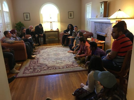 McMurry University students enjoy an interfaith gathering, featuring an international dinner, at the home of Robert Wallace, a sociology professor.