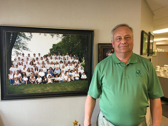 Ron Van Den Heuvel stands in his De Pere offices in 2017 next to a photo of his extended family.