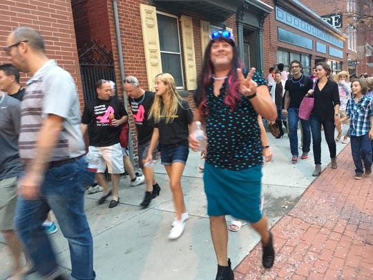Gregg Doutrich of electrical company team, Gettle Team, Inc. throws up a peace sign as he walks his first year at Walk A Mile In Her Shoes on Friday, Oct. 6.