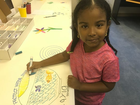 Layla, 5, draws a fish at the Liquid Earth water sustainability