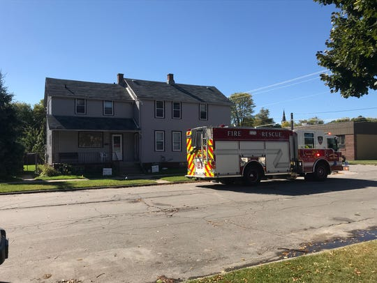 Firefighters investigate a reported arson at a home