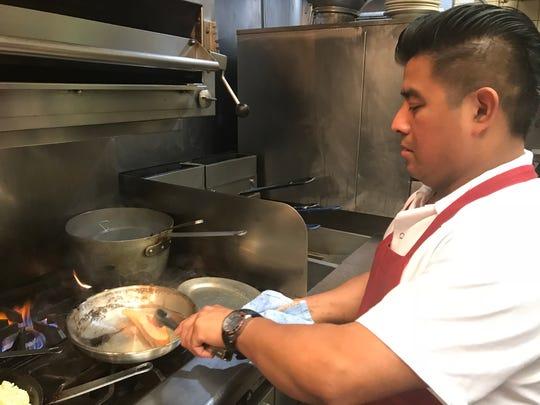 Palmer's Steakhouse's head line cook Elias Mendoza prepares the restaurant's pan-seared Ora king salmon.