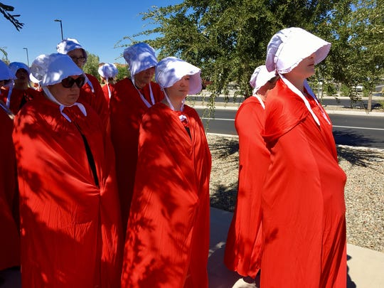 Members of Stronger Together Arizona donned white caps and red capes to protest restrictions on women's reproductive rights outside a gathering of Republicans in Mesa on Oct. 7.