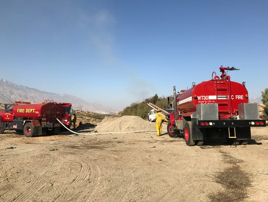 Cal Fire crews work a debris fire on a vacant property